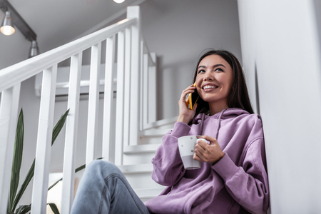 Cheerful woman. Cheerful young woman calling her boyfriend while drinking tea at home
