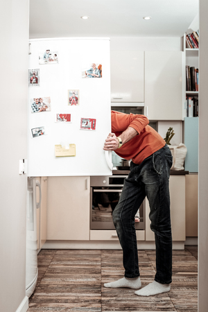 Hungry husband. Hungry husband wearing jeans opening refrigerator after coming home from work 免版税图像