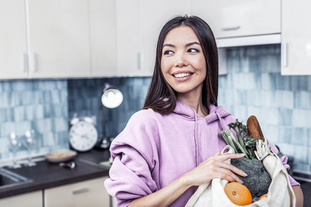 Standing in kitchen. Close up of dark-haired beautiful family woman standing in kitchen holding bag with vegetables