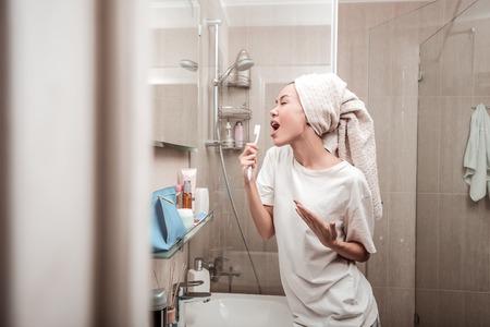 Como una estrella del pop. Encantado de mujer positiva cantando en el baño mientras está de pie frente al espejo