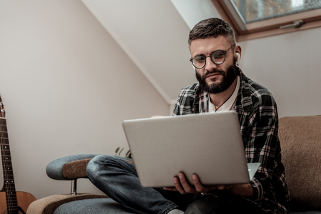 Smart young man looking at the laptop screen while working as a freelancer Stock Photo