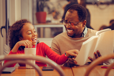 Interesting funny book. Father and daughter laughing while reading interesting funny book together Imagens - 117797284
