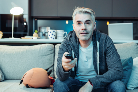 News time. Grey-haired bearded attractive man wearing sportswear watching tv Stock Photo