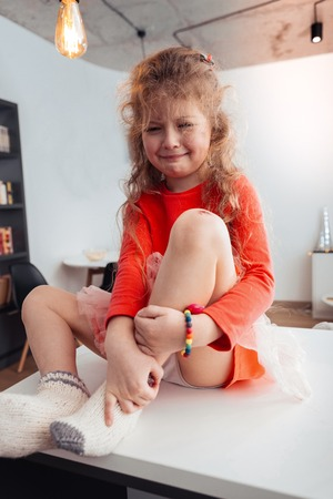 Girl on the table. Cute small long-haired girl wearing thick socks sitting on the table