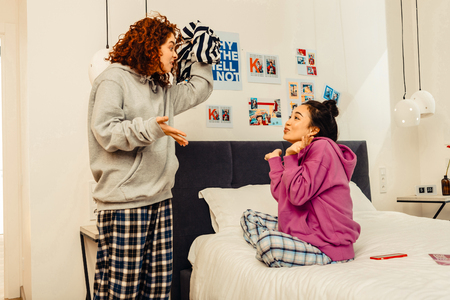 Fight for sweater. Two funny young roommates having fight for nice striped sweater Stock Photo