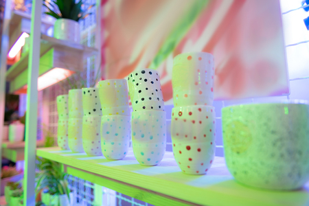 Dotted empty pots. Fashionable hand-made pots being shown on shelves of shop and waiting for customers and plants