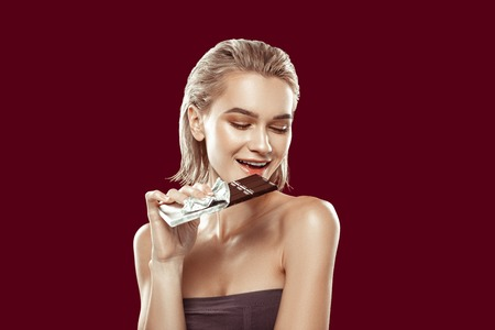 Biting piece. Young slim appealing model smiling while biting piece of dark chocolate