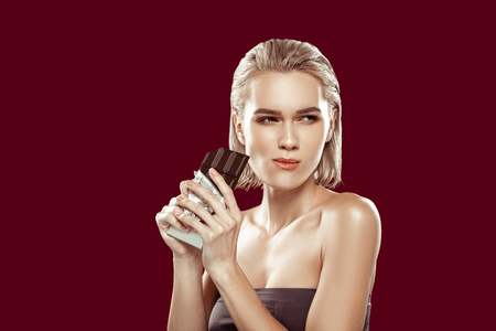 Chewing dark chocolate. Young appealing blonde-haired model standing near red wall chewing dark chocolate 免版税图像