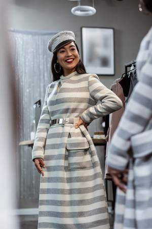 Good looks. Young asian beaming woman in a striped coat looking happy while posing in front of the mirror