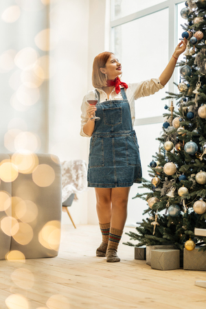 Ornaments. Beautiful red-haired girl with big earrings touching the christmas tree ornament standing near the christmas tree