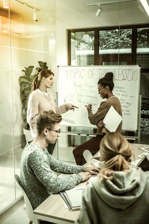 Standing near blackboard. Blonde-haired student with ponytail standing near blackboard talking to her teacher