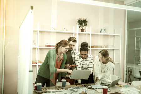 Overloaded with work. Four office workers wearing casual clothes feeling overloaded with a lot of work Stock Photo