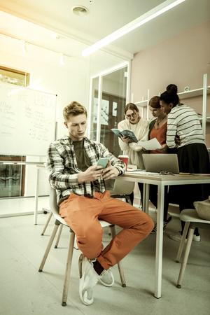 Social media. Blonde student wearing orange trousers sitting in social media instead of group brainstorming