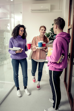 Break between classes. Three students wearing casual nice clothes having coffee break between classes