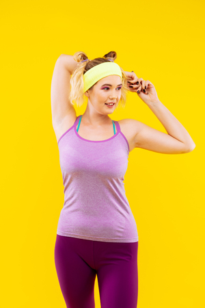 Stretching muscles. Blonde-haired woman wearing yellow head band stretching her muscles Stock Photo