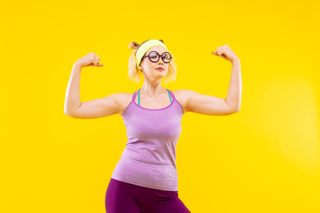 Showing muscles. Blonde-haired young appealing woman wearing glasses showing her muscles