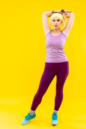 Purple leggings. Blonde-haired appealing woman wearing purple leggings and blue sneakers Stock Photo
