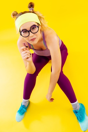 Woman in glasses. Top view of young woman wearing glasses and colorful clothes eating candy Stock Photo