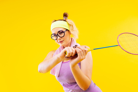 Tennis racket. Blonde-haired young positive woman wearing glasses holding tennis racket Stock Photo