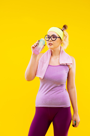 Thirsty after tennis. Blonde-haired woman drinking water while feeling thirsty after tennis