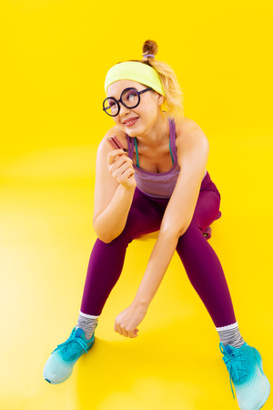 Eating candy. Young blonde-haired woman wearing glasses sitting on skate and eating candy