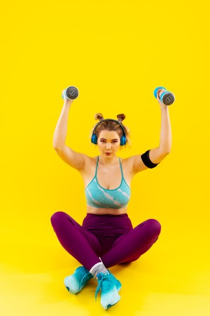 Exercises for arms. Blonde-haired woman losing weight sitting on floor and doing exercises for arms