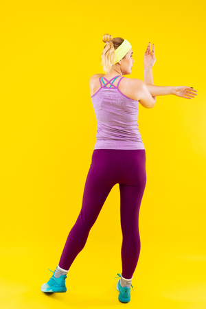 Stretching arms. Slim appealing blonde-haired woman wearing purple leggings stretching her arms