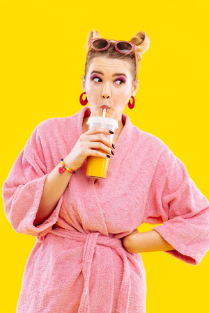 Morning juice. Blonde-haired woman wearing pink bathrobe and sunglasses drinking morning juice Фото со стока - 117284128