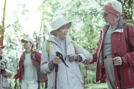 Cheerful seniors. The couple of seniors enjoying spending time hiking in the forest