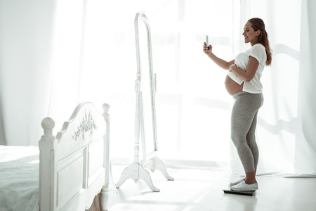 In mirror reflection. Appealing positive woman with round pregnant stomach making photo of herself while standing on weights 版權商用圖片