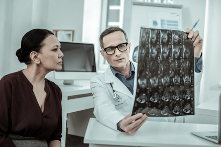 Patient attentively looking. Demonstrative medical worker showing x-ray photo to patient explaining situation with her health