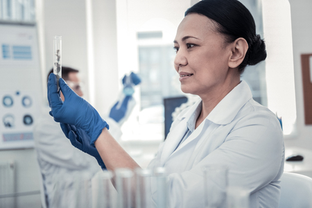 Female biologist. Motivated and concentrated woman is studying the plant Stock Photo - 117215076