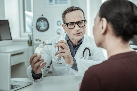 Using heart model. Confused doctor holding gypsum model of the main organ of the person being demonstrative Reklamní fotografie - 117214527