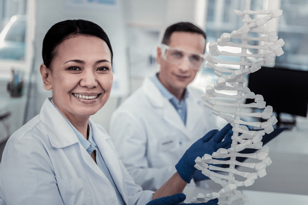 Decoding the DNA. Smiling female scinetist working with the model of DNA