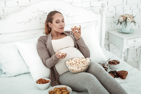 Bunch of food. Thick expectant woman in pastel outfit lying in bed and carrying donut being surrounded with sweets and snacks Stock Photo