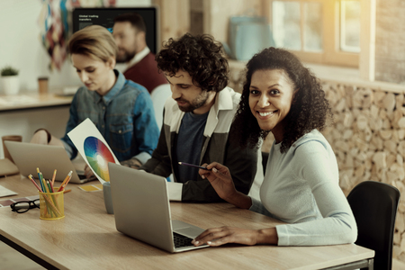 Working with pleasure. Beautiful African American long-haired woman smiling happily while having discussion with her colleague Banque d'images