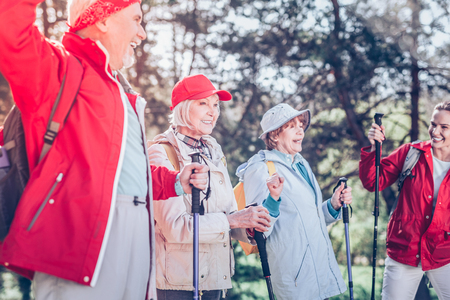 Nordic walking. Group of active retired people fond of Nordic walking resting in forest together
