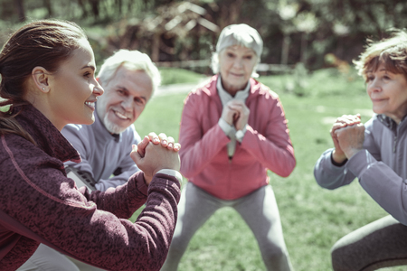 Uneven-aged lady. Uneven-aged smart nice lady preparing for difficult gymnastic while having work out in park near their gym 스톡 콘텐츠 - 117798398