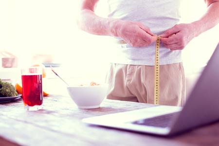 Measuring waistline. Modern mature man working on improvement of his body measuring waistline in the morning Foto de archivo - 117798464