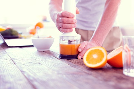 Morning juice. Close up of man using his modern blender while squeezing morning orange juice for healthy breakfast