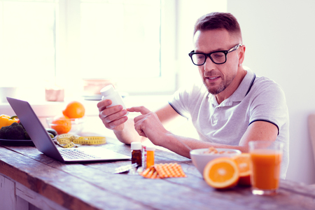 Supplements and vitamins. Man wearing glasses leading healthy lifestyle reading the information about supplements and vitamins