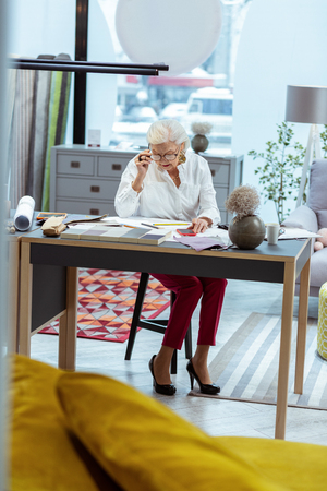 Meticulous studying. Successful elderly trendy worn CEO in glasses and grey hair meticulous studying papers at her table Фото со стока - 117798554