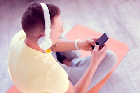 On sport rag. Bearded handsome blonde-haired man sitting on sport rag while listening to music in earphones