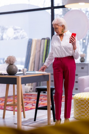 Fancy businesswoman. Beautiful stylish female entrepreneur in years with short grey haircut in white shirt and trendy fuschia trousers standing near office table and studying documents on the table.