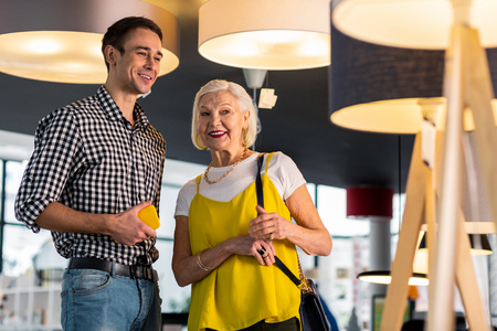 Doing shopping couple. Beaming gorgeous senior lady in trendy clothes lively discussing lamps buying in the lighting shop with younger attractive smiling tall beau