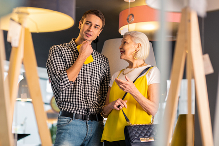 Couple at store. Bewitching smiling aged woman in stylish clothes and yellow massive earrings lovingly looking at younger handsome gallant brown-haired beau Stockfoto