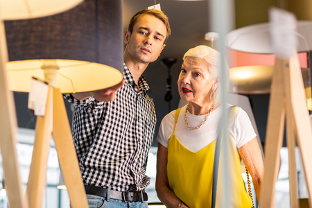Buying standard-lamp. Beauteous aged madam wearing fancy top, t-shirt, massive accessories and attractive dark-haired mature man in checked blue shirt considering buying standard-lamps in showroom.