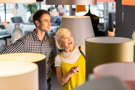 Couple in lighting store. Delightful elderly grey-haired fashionable madam paying her younger attractive beaming boyfriend attention to the lamp she liked