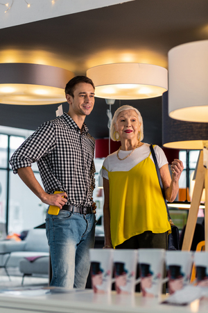 Aging lady with younger boyfriend. Charming stylish aging grey-haired woman in trendy clothing being in lighting store with alluring beaming tricenarian boyfriend in blue shirt
