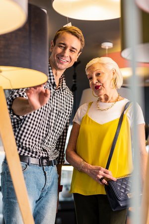 Loving couple at store. Stunner brown-haired smiling man of thirty enthusiastically showing a floor-lamp he liked to his elderly charming grey-haired beloved in fancy clothes.